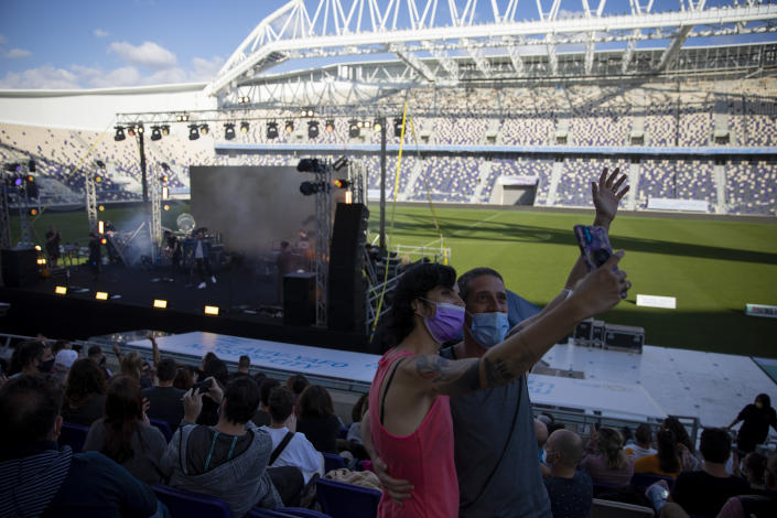 "Audience members wearing protective face masks take a selfie during a performance of Israeli musician Ivri Lider, where all guests were required to show ""green passport"" proof of receiving a COVID-19 vaccination or full recovery from the virus at a soccer stadium in Tel Aviv, Friday, March. 5, 2021. (AP Photo/Oded Balilty)"