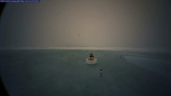 A picture of a buoy anchored near a remote webcam at the North Pole shows a meltwater lake surrounding the camera on July 22.