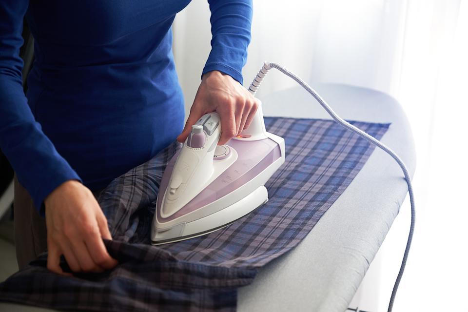 A person irons a shirt.