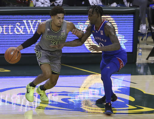 Baylor guard MaCio Teague (31) drives against Kansas guard Marcus Garrett (0) in the first half of an NCAA college basketball game, Monday, Jan. 18, 2021, in Waco, Texas. (AP Photo/Jerry Larson)