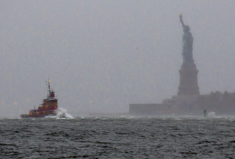 Waves crash over the bow of a tug boat as it passes near the Statue of Liberty in New York Monday, Oct. 29, 2012 as rough water as the result of Hurricane Sandy churned the waters of New York Harbor. Hurricane Sandy continued on its path Monday, forcing the shutdown of mass transit, schools and financial markets, sending coastal residents fleeing, and threatening a dangerous mix of high winds and soaking rain. (AP Photo/Craig Ruttle)
