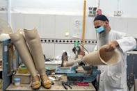 A technician works on prosthetic leg at the International Committee of Red Cross Rehabilitation Centre in Kabul (AFP/BULENT KILIC)