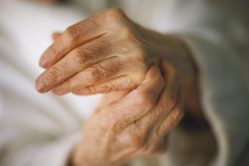 An elderly person holding their own hand as if in pain.