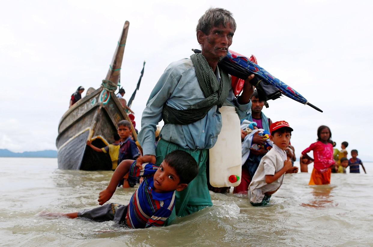A Rohingya refugee man pulls a child as they walk to the shore after crossing the Bangladesh-Myanmar border by boat through the Bay of Bengal in Shah Porir Dwip, Bangladesh, on Sept. 10, 2017.