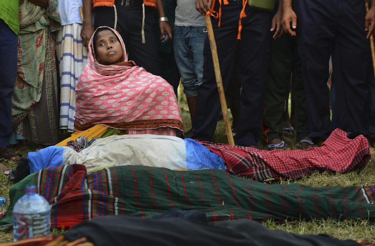 An unidentified Bangladeshi woman sits near bodies of victims on the banks of the River Meghna after a ferry carrying more than 100 passengers capsized and sank after being hit by a storm in Munshiganj district, Bangladesh, Thursday, May 15, 2014. According to an official eight bodies have been recovered and there was confusion about the number of missing people. (AP Photo/Sony Ramany)