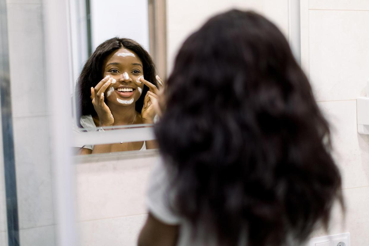 woman applying beauty products looking in the mirror