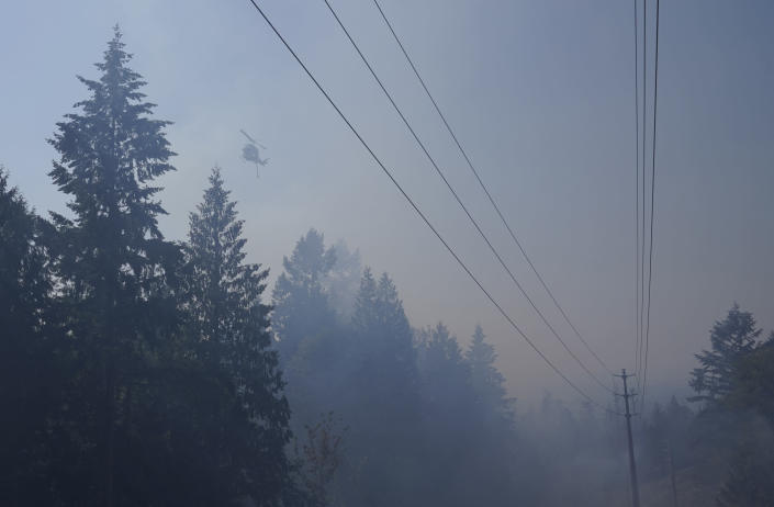 A water-drop helicopter flies Wednesday, Sept. 9, 2020, near a wildfire burning in Bonney Lake, Wash., south of Seattle. (AP Photo/Ted S. Warren, Pool)