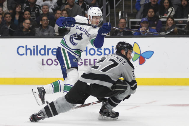 Vancouver Canucks' Elias Pettersson, top, of Sweden, and Los Angeles Kings' Alec Martinez watch the puck hit by Pettersson enter the net for a goal during the third period of an NHL hockey game Saturday, Nov. 24, 2018, in Los Angeles. (AP Photo/Jae C. Hong)