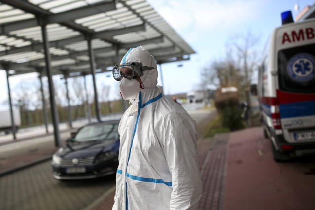 A health worker in a mask and protective suit waits to take passengers' temperature at the German-Polish border in Swiecko, Poland, on 11 March. (Getty Images)