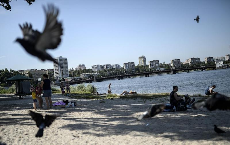 People relax near the Donbas river in Donetsk, Ukraine, on July 24, 2014 (AFP Photo/Bulent Kilic)