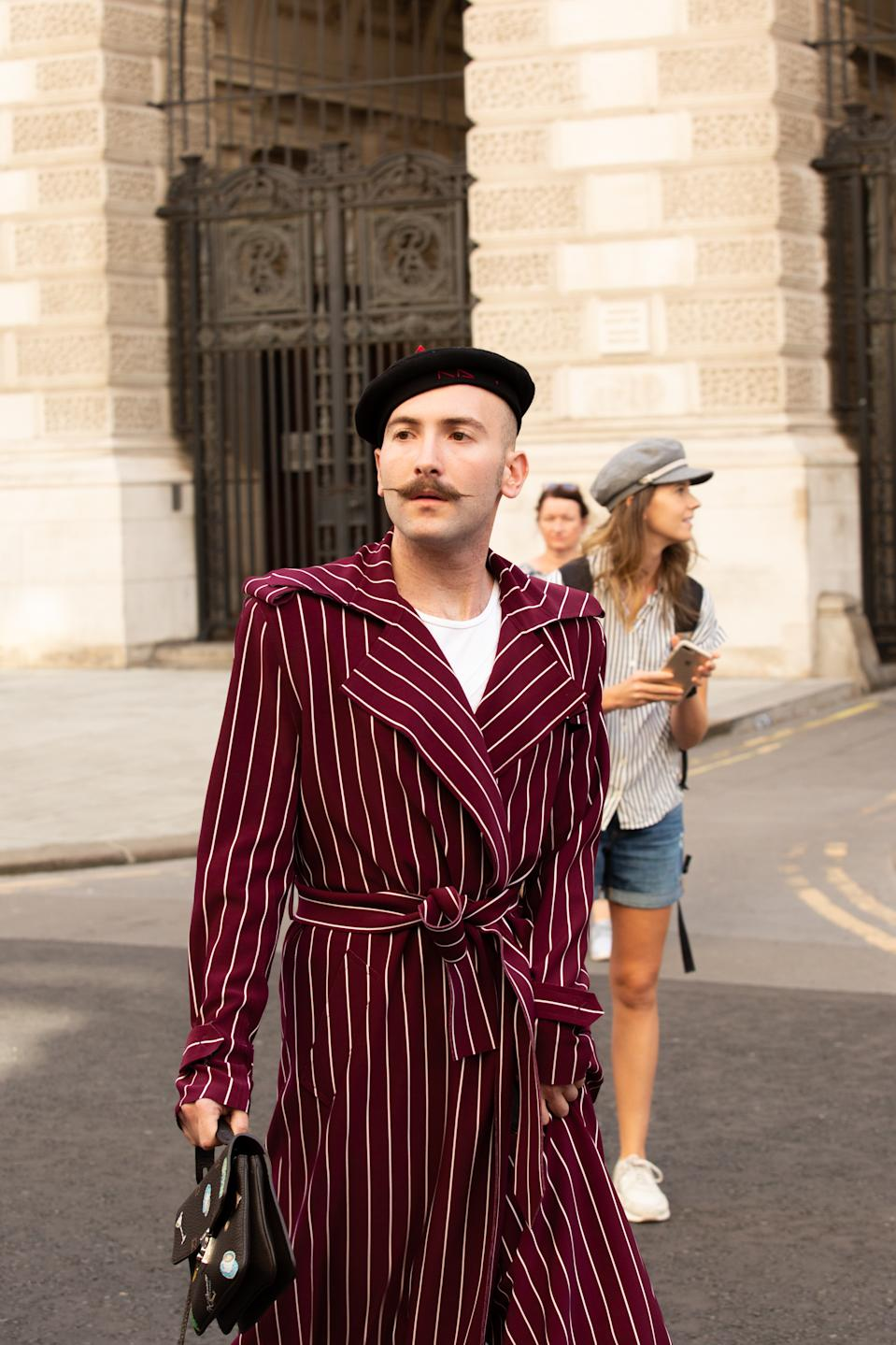A guest is seen wearing a striped coat and beret. [Photo: PA]