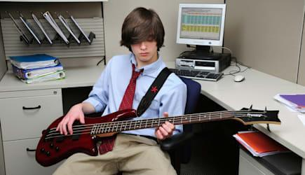 Young millenial office worker goofing off playing a bass guitar in his cubicle