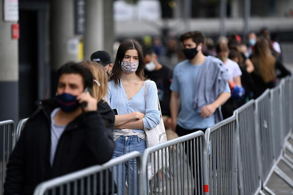Members of the public queue to receive a dose of a Covid-19 vaccine outside a temporary vaccination centre set up a the Emirates Stadium (AFP via Getty Images)