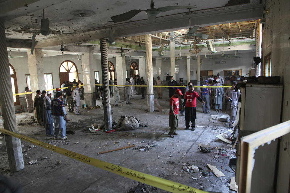 Rescue workers and police officers examine the site of a bomb explosion in an Islamic seminary in Peshawar, Pakistan, Tuesday, Oct. 27, 2020. A powerful bomb blast ripped through the Islamic seminary on the outskirts of the northwest Pakistani city of Peshawar on Tuesday morning, killing some students and wounding dozens others, police and a hospital spokesman said. (AP Photo/Muhammad Sajjad)