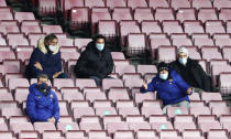 Barcelona's Lionel Messi, center, watches the Spanish La Liga soccer match between Barcelona and Eibar from the stands of the Camp Nou stadium in Barcelona in Barcelona, Spain, Tuesday, Dec. 29, 2020. (AP Photo/Joan Monfort,)