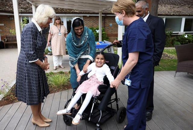 The Duchess of Cornwall meets parents Vaida and Aqsad Ali and their daughter Fatima, nine, during a visit to the Helen & Douglas House children's hospice in Oxford