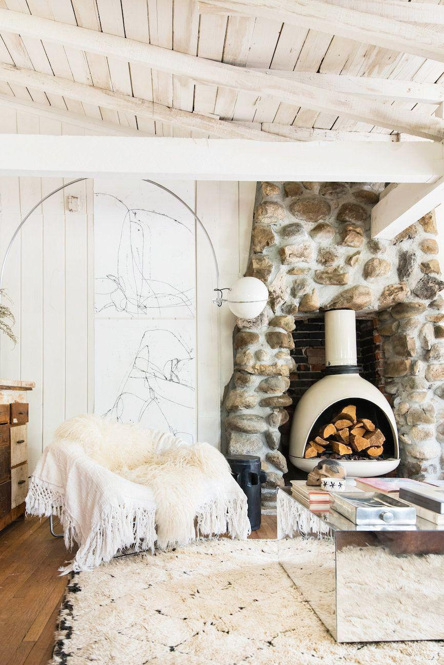 <p>If you want to emulate the worn look of the white wood ceiling in this mod California living room designed by Leanne Ford Interiors, opt for a lime wash instead of a classic paint. The whole space, from the retro wood burning fireplace and stone hearth to the sheepskin throw, is very Flintstone-chic. </p>