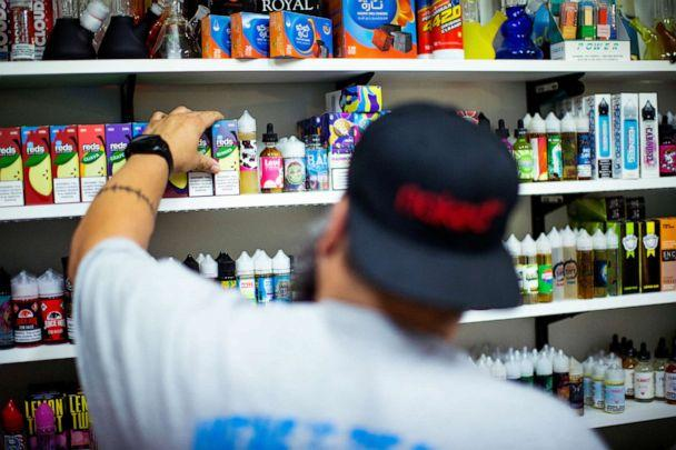 PHOTO: A vape shop worker organizes electronic smoking products in a local store in Jersey City, N.J., Sept. 12, 2019. (Eduardo Munoz/Reuters)