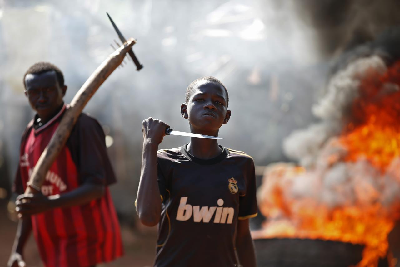 A boy gestures in front of a barricade on fire during a protest after French troops opened fire at protesters blocking a road in Bambari May 22, 2014. REUTERS/Goran Tomasevic (CENTRAL AFRICAN REPUBLIC - Tags: CIVIL UNREST POLITICS TPX IMAGES OF THE DAY MILITARY)