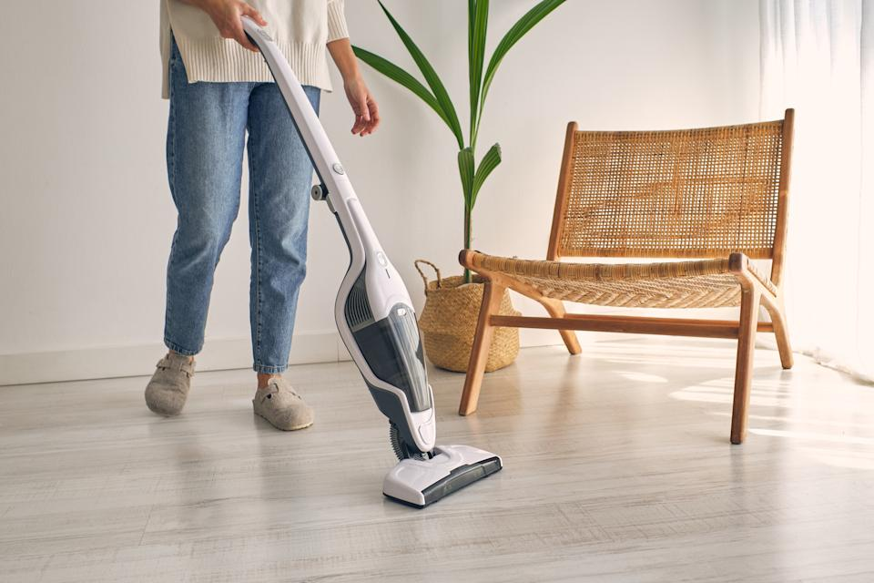 Woman in jeans and slippers at home, cleaning the floor with a cordless broom vacuum cleaner.