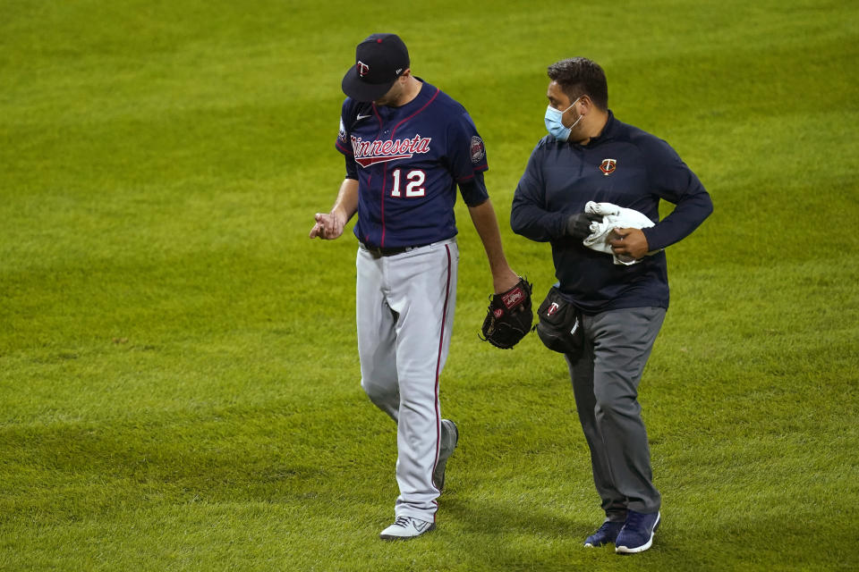 Minnesota Twins starting pitcher Jake Odorizzi looks at his pitching hand as he leaves the baseball game with a trainer during the fourth inning against the Chicago White Sox on Wednesday, Sept. 16, 2020, in Chicago. (AP Photo/Charles Rex Arbogast)
