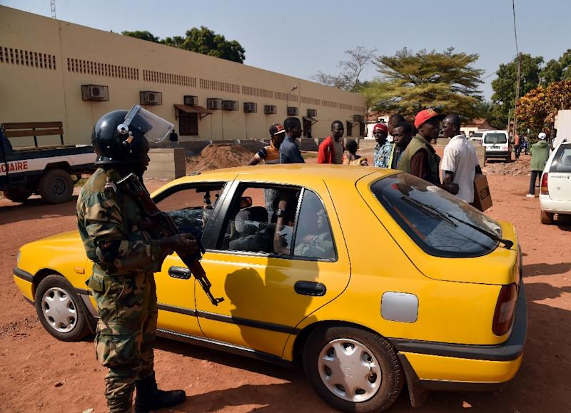 A Central African Republic police officer talks with a taxi driver outside a vote-counting centre for the presidential and parliamentary elections on January 2, 2016 in Bangui
