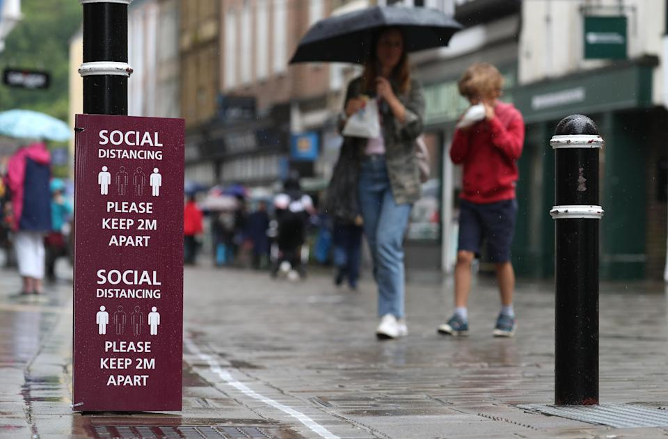 People walk past a social distancing sign on Winchester High street, as further coronavirus lockdown restrictions are lifted in England. (AP)