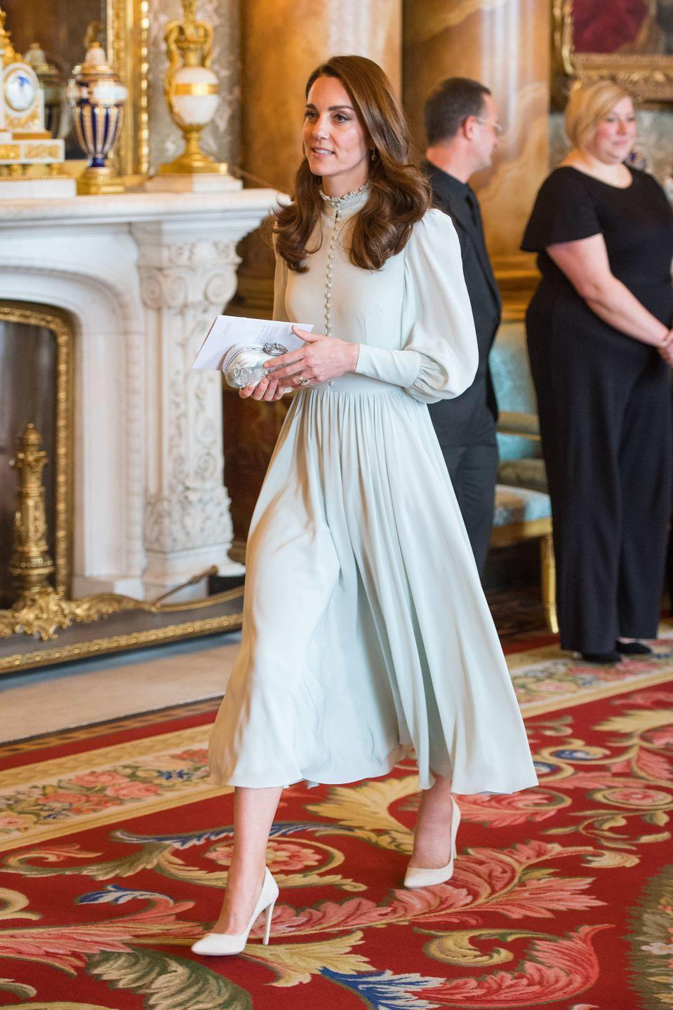 """<p>The Duchess wore <a href=""""https://www.townandcountrymag.com/style/fashion-trends/a26630013/kate-middleton-blue-dress-princes-charles-investiture-anniversary/"""" rel=""""nofollow noopener"""" target=""""_blank"""" data-ylk=""""slk:a pale blue dress"""" class=""""link rapid-noclick-resp"""">a pale blue dress</a> with nude heels and a small clutch to a celebration at Buckingham Palace in honor of the <a href=""""https://www.townandcountrymag.com/society/tradition/a26576659/prince-charles-prince-wales-investiture-1969-true-story/"""" rel=""""nofollow noopener"""" target=""""_blank"""" data-ylk=""""slk:50th anniversary of Prince Charles's investiture"""" class=""""link rapid-noclick-resp"""">50th anniversary of Prince Charles's investiture</a> as the Prince of Wales.</p>"""