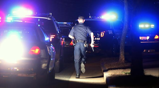 WATERTOWN, MA - APRIL 19: A police officer runs with his gun drawn while searching for a suspect on April 19, 2013 in Watertown, Massachusetts. Earlier, a Massachusetts Institute of Technology campus police officer was shot and killed late Thursday night at the school's campus in Cambridge. A short time later, police reported exchanging gunfire with alleged carjackers in Watertown, a city near Cambridge. According to reports, one suspect has been killed during a car chase and the police are seeking another - believed to be the same person wanted in connection with the deadly bombing at the Boston Marathon earlier this week. (Photo by Mario Tama/Getty Images)