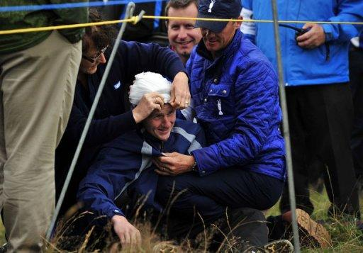 16 year old spectator, Jason Blue is helped after being struck on the head by a ball hit by Rory McIlroy of Northern Ireland on the 15th hole during his first round on the opening day of the 2012 Open Championship at Royal Lytham and St Annes in Lytham