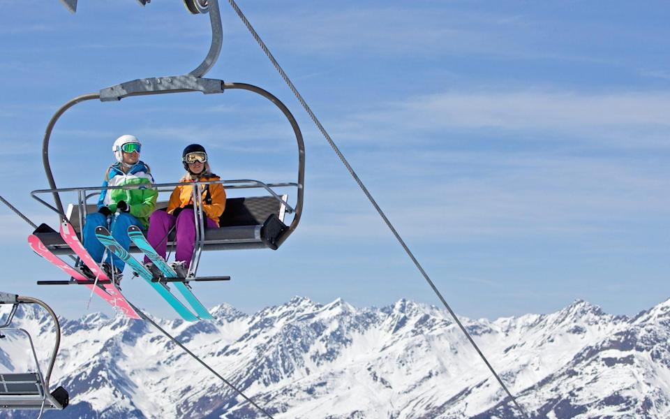 two girls in ski lift with colourful skis - Christoph Jorda /The Image Bank RF