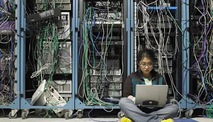 Young woman using laptop in server room