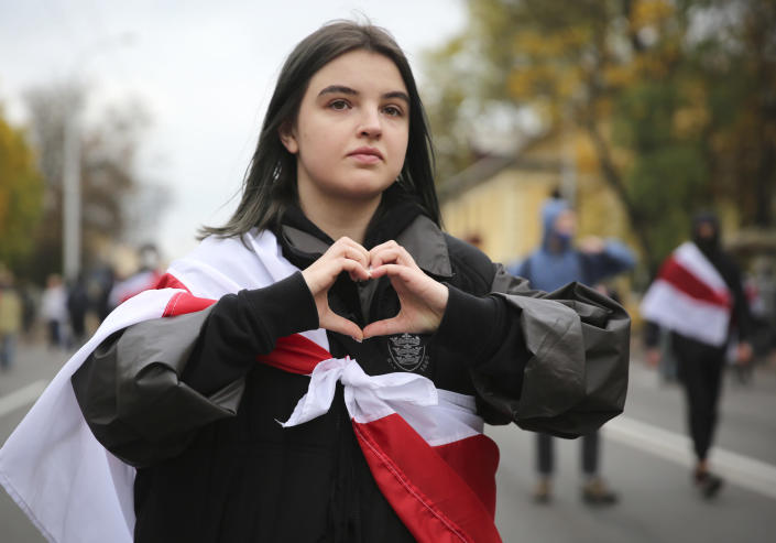 A woman draped in an old Belarusian national flag gestures during an opposition rally to protest the official presidential election results in Minsk, Belarus, Sunday, Oct. 25, 2020. The demonstrations were triggered by official results giving President Alexander Lukashenko 80% of the vote in the Aug. 9 election that the opposition insists was rigged. Lukashenko, who has ruled Belarus with an iron fist since 1994, has accused the United States and its allies of fomenting unrest in the ex-Soviet country. (AP Photo)