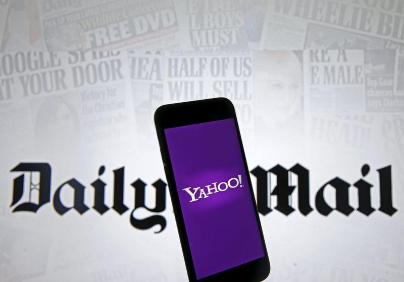 Smartphone with Yahoo logo is seen in front of a displayed Daily Mail logo