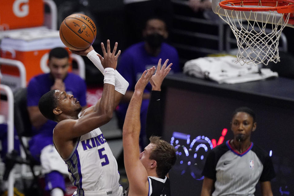 Sacramento Kings guard De'Aaron Fox, left, shoots as Los Angeles Clippers guard Luke Kennard defends during the first half of an NBA basketball game Sunday, Feb. 7, 2021, in Los Angeles. (AP Photo/Mark J. Terrill)