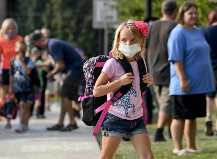 A girl wearing a mask heads to school past adults without masks.