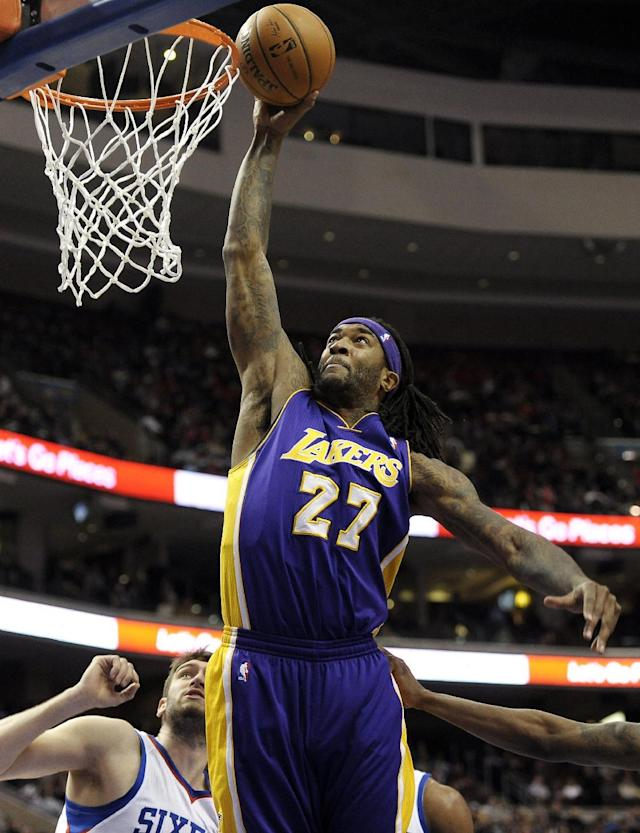 Los Angeles Lakers' Jordan Hill (27) dunks over Philadelphia 76ers' Spencer Hawes during the first half of an NBA basketball game on Friday, Feb. 7, 2014, in Philadelphia. (AP Photo/Michael Perez)