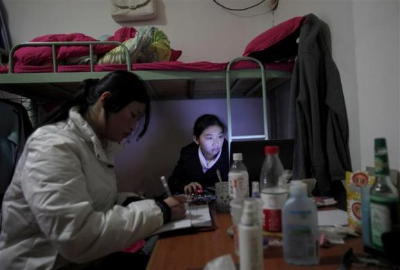 A young graduate worker uses a laptop in her room at a residence hotel in a suburban area of Shanghai December 10, 2010.