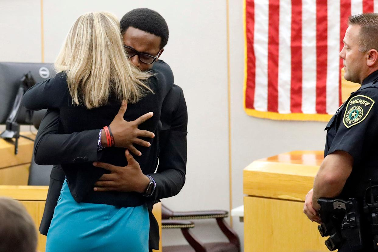 Botham Jean's younger brother, Brandt, hugs former Dallas police officer Amber Guyger after she was sentenced to 10 years.