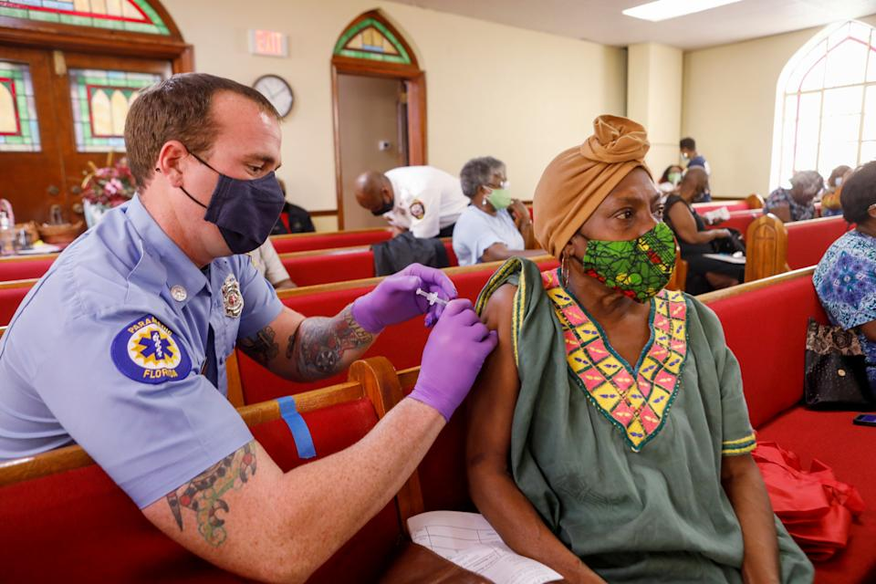 A woman, seated on a church pew, receives a shot in the arm by a paramedic, both wearing face masks