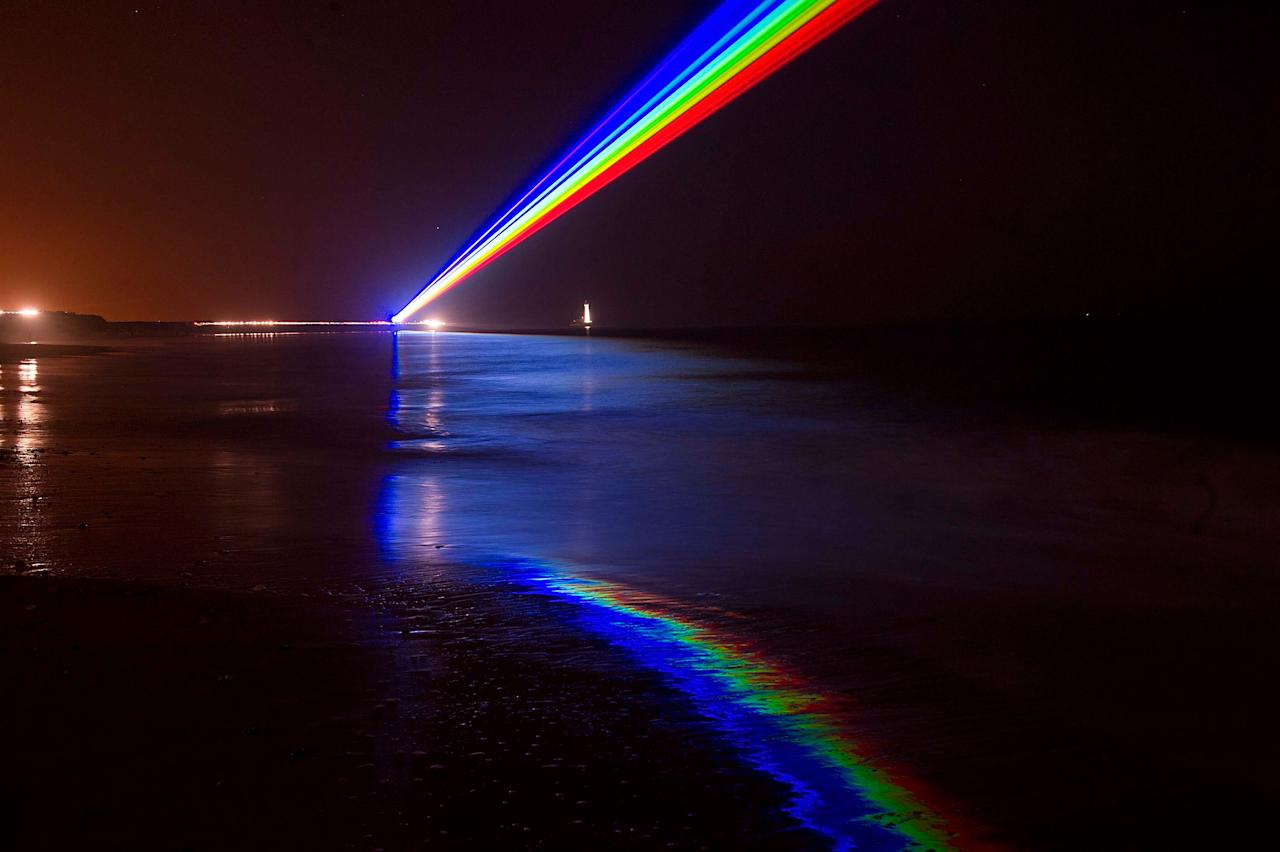 WHITLEY BAY, ENGLAND - MARCH 01:  International artist Yvette Mattern shows his stunning laser rainbow projection, Global Rainbow, on March 1, 2012 in Whitley Bay, England. The light installation celebrates the London 2012 Cultural Olympiad in the north-east of England. The Global Rainbow has previously lit up the skies of Germany, France and the United States. The projection will shine along the North Tyneside coastline for 4 days, before moving to other locations in the UK. (Photo by Bethany Clarke/Getty Images)