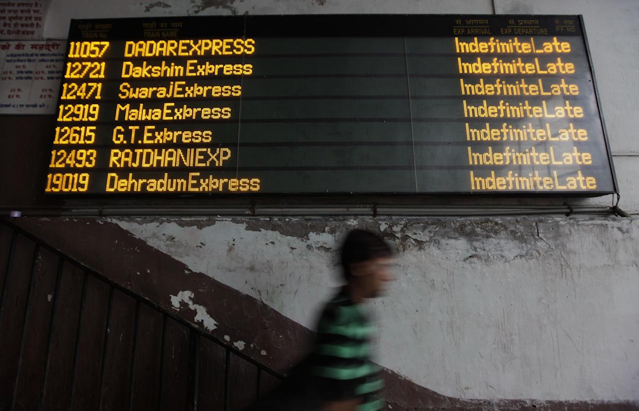 "An Indian commuter walks past the status board for trains displaying ""Indefinite Late"" for all the trains following the power outage that struck in the early hours of Monday, July 30, 2012, at a train station in New Delhi, India. Northern India was plunged into darkness Monday after a supply grid tripped because of overloading, officials said. (AP Photo/Altaf Qadri)"