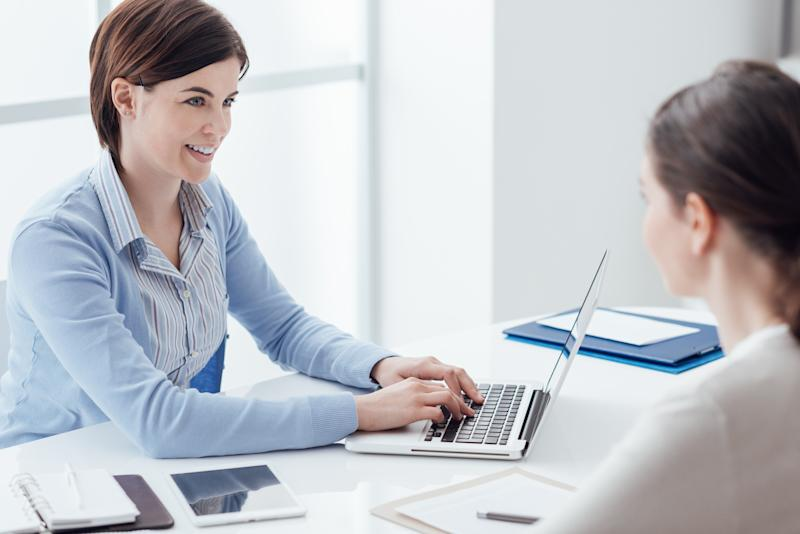 A human resources employee assists another employee in her office.
