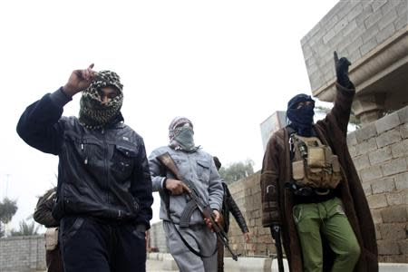Gunmen fighters walk in the Gunmen fighters walk in the streets of the city of Falluja, 50 km (31 miles) west of Baghdad
