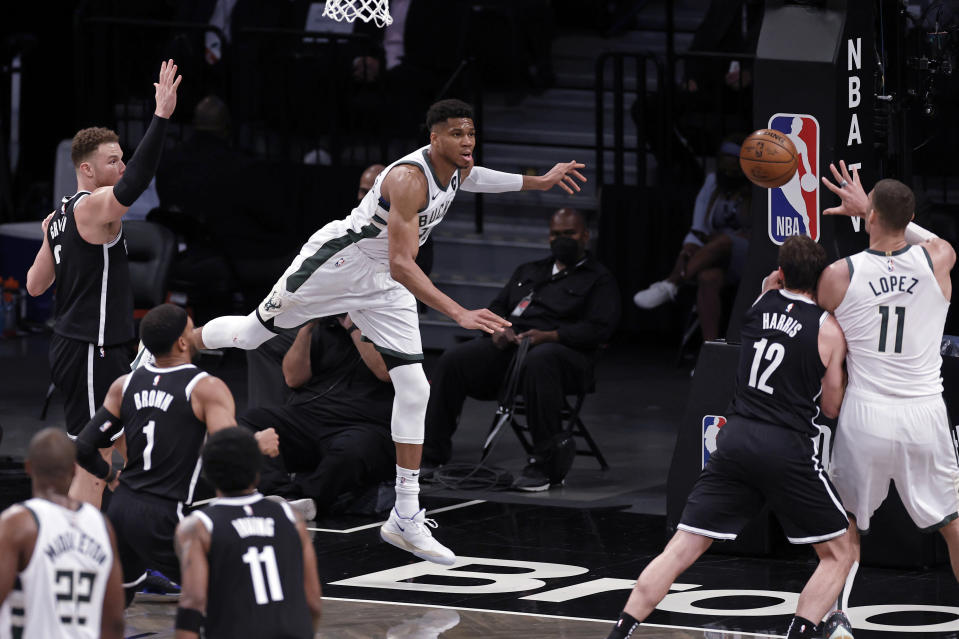 Milwaukee Bucks forward Giannis Antetokounmpo passes the ball to Brook Lopez (11) in front of Brooklyn Nets forward Joe Harris (12) during the second half of Game 1 of an NBA basketball second-round playoff series Saturday, June 5, 2021, in New York. The Nets won 115-107. (AP Photo/Adam Hunger)
