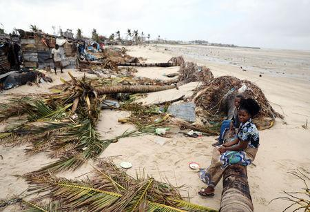 Children sit amongst storm debris left in the aftermath of Cyclone Idai, in Beira, Mozambique March 23, 2019. REUTERS/Siphiwe Sibeko