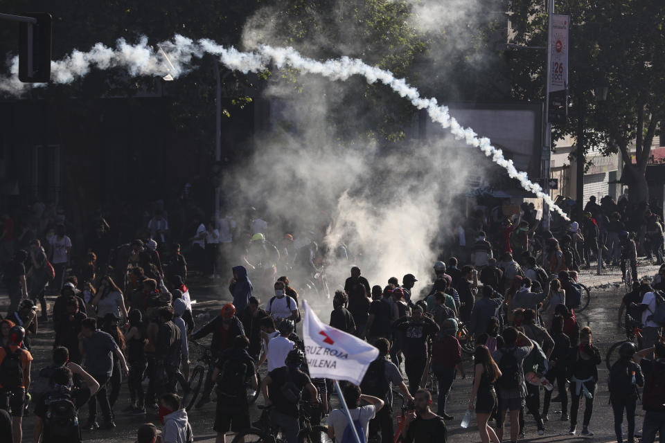 Demonstrators clash with police launching tear gas as a state of emergency remains in effect in Santiago, Chile, Sunday, Oct. 20, 2019. Protests in the country have spilled over into a new day, even after President Sebastian Pinera cancelled the subway fare hike that prompted massive and violent demonstrations. (Photo: Esteban Felix/AP)