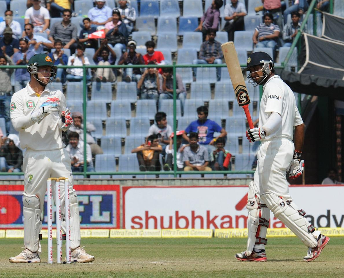India's Cheteshwar Pujara raises his bat to acknowledge applause for his half century on Day two of the 4th Test of the Border-Gavaskar Trophy, at Feroz Shah Kotla Stadium in Delhi on March 23, 2013. P D Photo by P S Kanwar