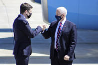 U.S. Rep. Bryan Steil, R-Janesville, and Vice President Mike Pence fist bump each other as they meet on the tarmac following Pence's flight to the Southern Wisconsin Regional Airport, Wednesday, Aug. 19, 2020, in Janesville, Wis. Pence was on his way to speak at Tankcraft Corporation in Darien, Wis. (Ashley Mccullum/The Janesville Gazette via AP)