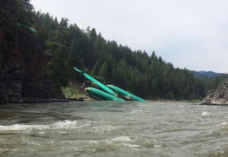 Three Boeing 737 fuselages lie on an embankment on the Clark Fork River after a BNSF Railway Co train derailed Thursday near Rivulet, Montana in this picture taken July 4, 2014. REUTERS/Andrew Spayth
